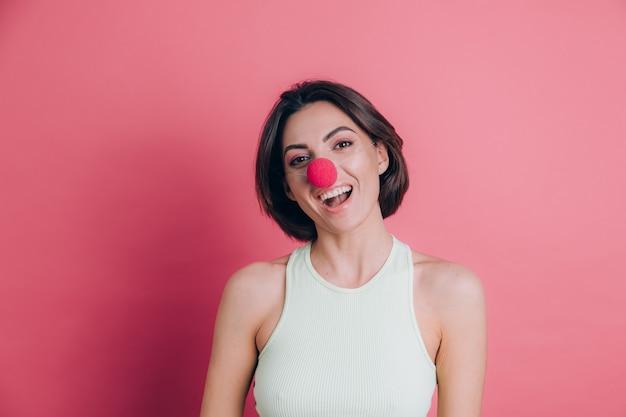 광대 코를 입고 분홍색 배경에 꽤 재미 있고 웃는 젊은 여자, 파티 분위기에 여자