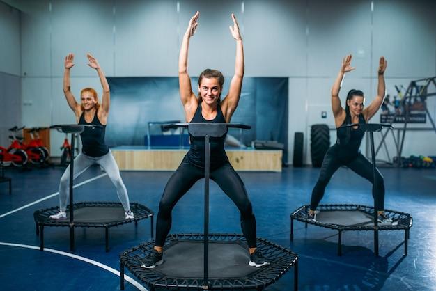 運動中のスポーツトランポリン、フィットネストレーニングの女性。ジムでの女性のチームワーク。有酸素クラス