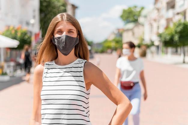 マスクが付いている通りの女性