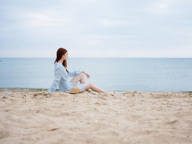 손에 모자와 바다 근처 sundress에 모래에 여자.