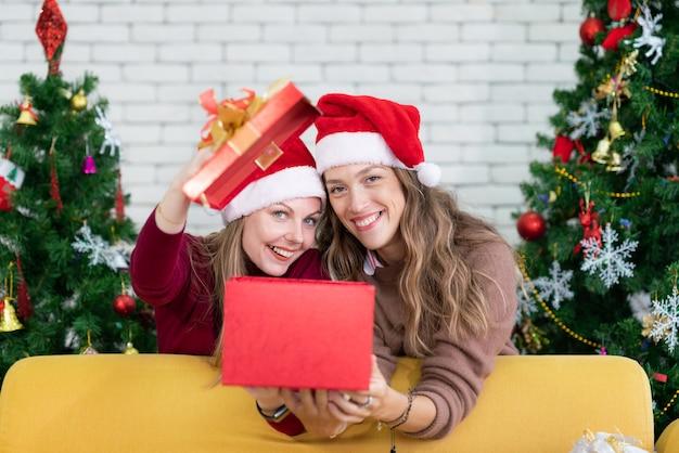 友人とクリスマスギフトボックスを開く女性。クリスマス休暇家族の概念。パーティーで楽しく祝う
