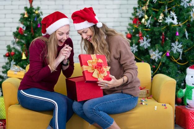 友人とクリスマスギフトボックスを開く女性。クリスマス休暇家族の概念。