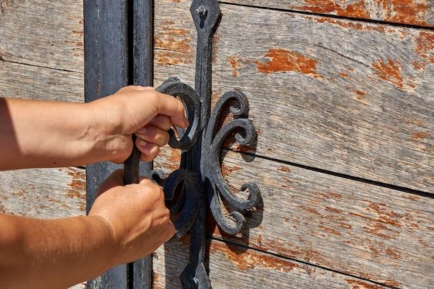 여자들은 연철 요소로 장식 된 고대 나무 문을 엽니 다. 철제 손잡이가 달린 오래된 자물쇠. 확대. 선택적 초점.
