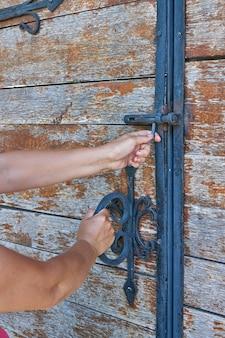 여자들은 연철 요소로 장식 된 고대 나무 문을 엽니 다.