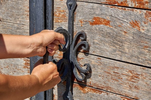 Women opens an ancient wooden door decorated with wrought iron elements. old lock with an iron handle. close-up. selective focus.