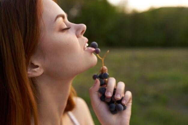 야외에서 포도를 먹는 여성 여름 방학