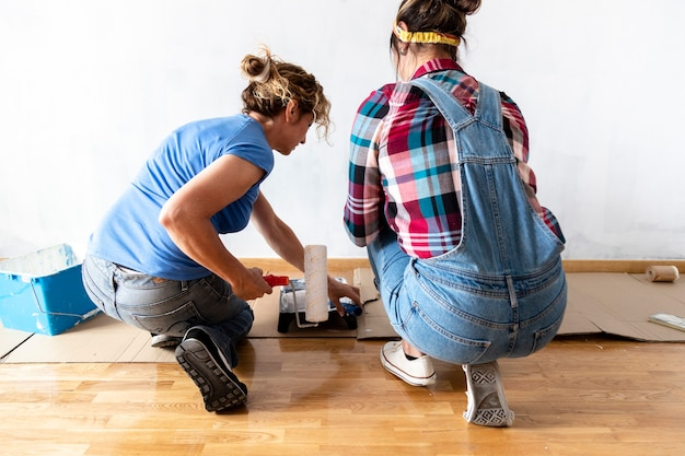 Women paint house walls renovating protect floors with cardboard moving in new apartment