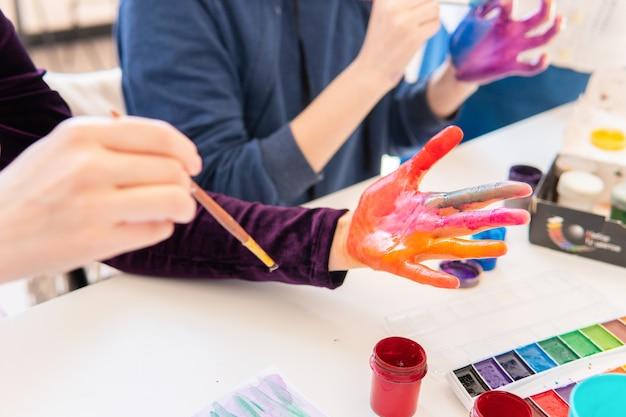 Женщины раскрашивают руки цветными красками в классе
