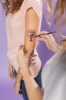 Women painting feminism symbol on arm