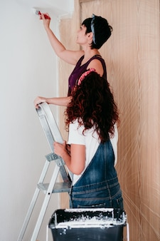 Women painting the room walls