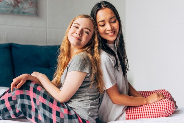 Women in pajamas sitting on bed
