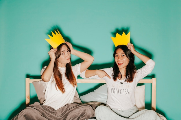 Women in paper crowns on bed