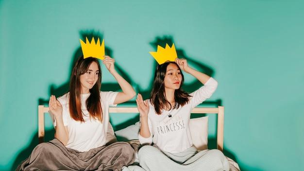 Women in paper crowns waving hands