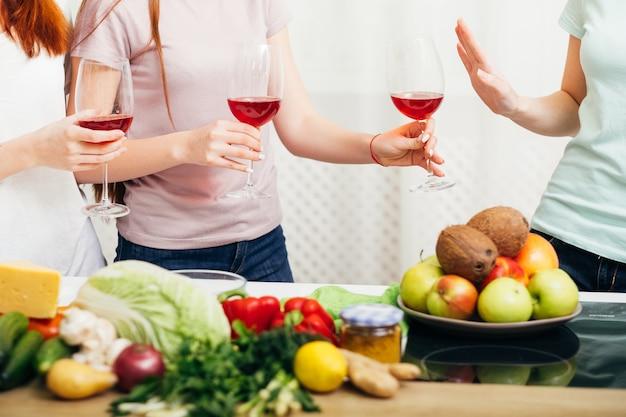 女性のパーティー。健康的なアルコールのないライフスタイル。赤ワイングラスを拒否する女の子。