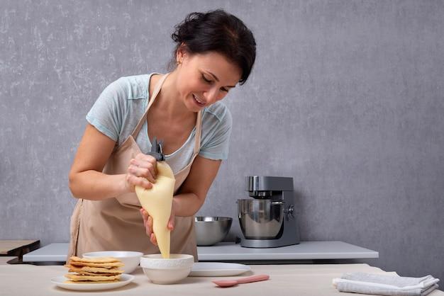 여성 생과자 요리사는 쇼트 케이크와 크림에서 케이크를 준비합니다. 케이크를 만드는 과정.