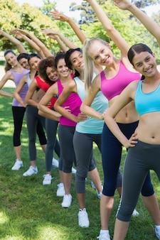 Женщины, выполняющие упражнения на растяжку в парке