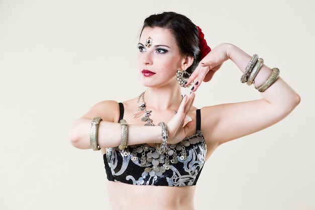 Women performs belly dance in ethnic dress on beige background, studio shot