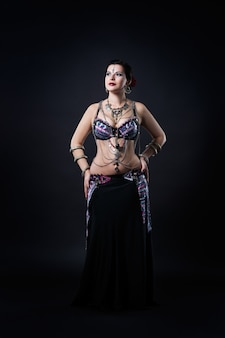 Women performs belly dance in ethnic dress on black background, studio shot