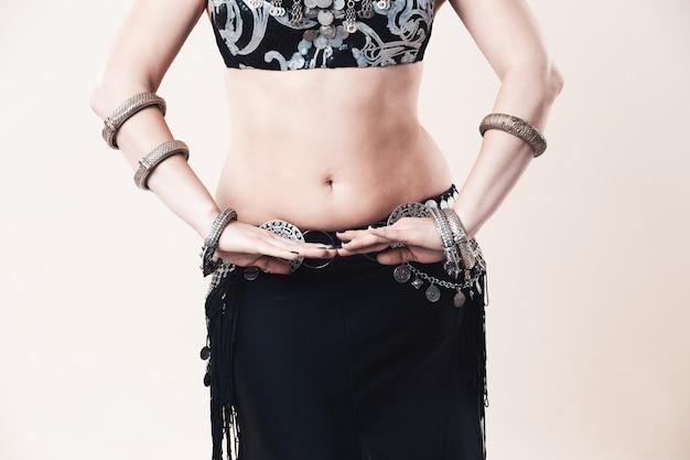 여자는 베이지 색 배경, 스튜디오 촬영에 민족 드레스 밸리 댄스를 수행