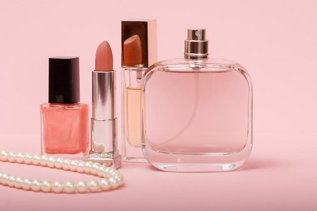 여성 향수, 구슬, 매니큐어와 립스틱이 분홍색 배경에 있는 병. 여성용 화장품과 향수.