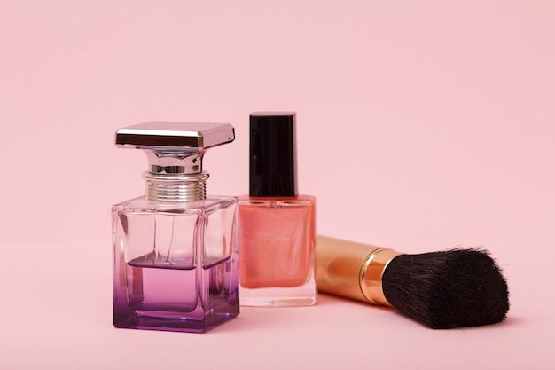 여성 향수, 매니큐어가 든 병, 분홍색 배경의 브러시. 여성용 화장품과 향수.