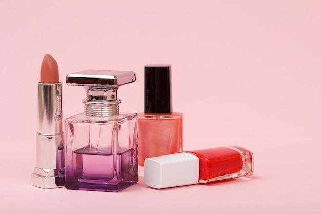 Женские духи, флаконы с лаком для ногтей и помады на розовом фоне. женская косметика и парфюмерия.