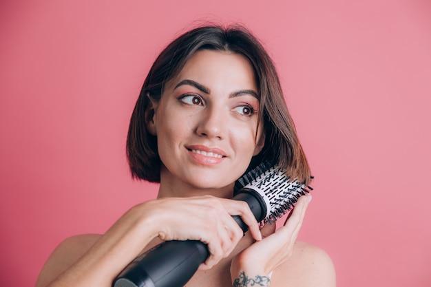 Le donne su sfondo rosa tengono l'asciugacapelli a spazzola rotonda per acconciare i capelli