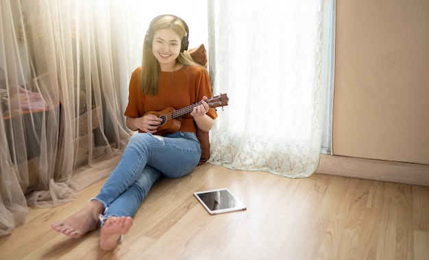 Women playing guitar in the living room at home