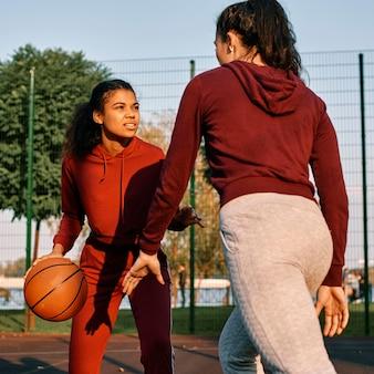 Женщины вместе играют в баскетбол