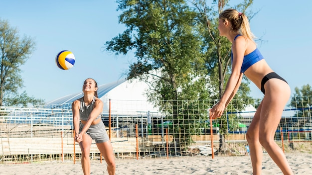 一緒にビーチでバレーボールをする女性