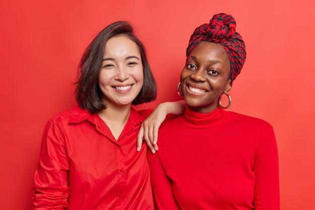 女性は、一般的な写真を幸せに笑顔にするためにポーズをとる良い気分で、鮮やかな赤でカジュアルに隔離された服を着て一緒に自由な時間を過ごします