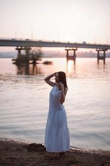 Женщины позируют на закате в полный рост портрет красивой молодой женщины, позирующей на закате на пляже ...