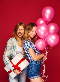 Женщины позируют с большой подарочной коробкой и розовыми шарами