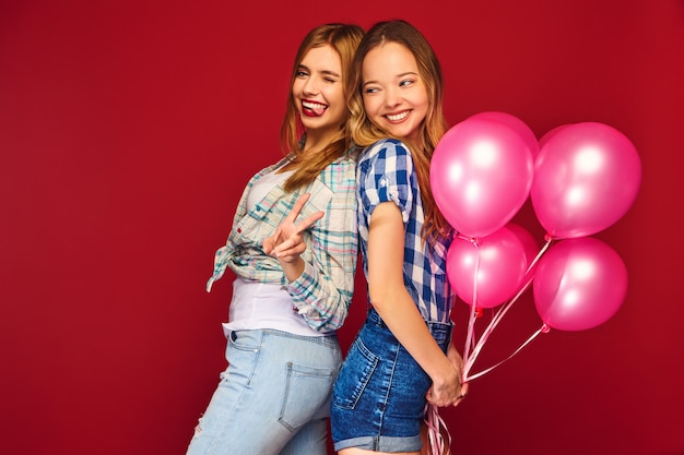 Women posing with big gift box and pink balloons