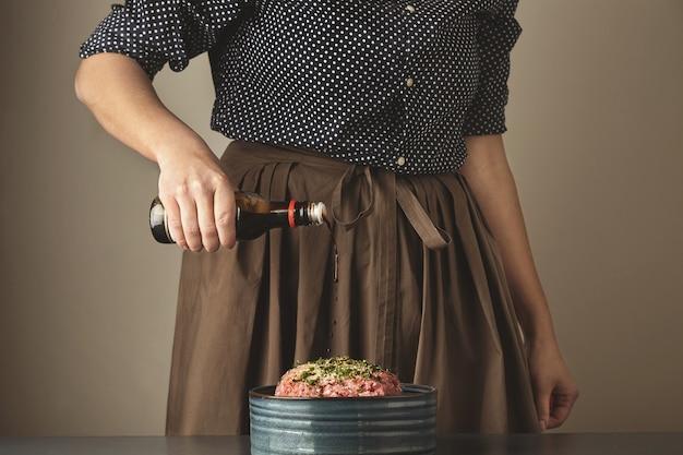 여성은 만두 또는 라비올리 요리를 위해 다진 고기에 간장 소스를 붓습니다.