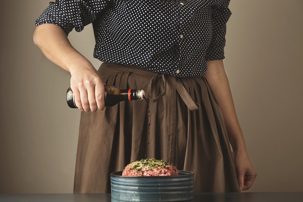 Women pours soy sause in minced meat for cooking dumplings or ravioli