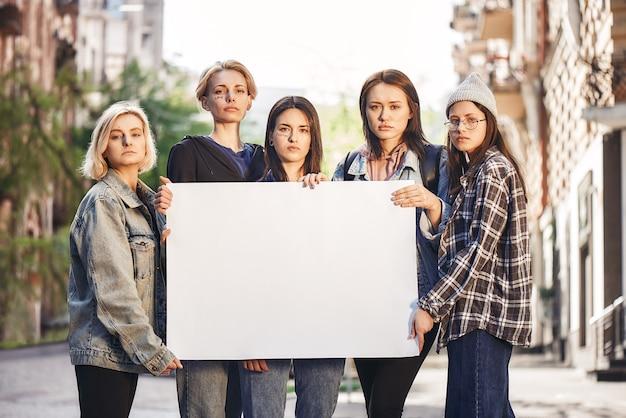 젊은 여성 활동가들의 여성 파워 그룹이 빈 간판을 들고 서 있다