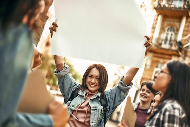 여자는 그녀의 머리 위에 빈 간판을 들고 웃 고 행복 한 젊은 여자 전원
