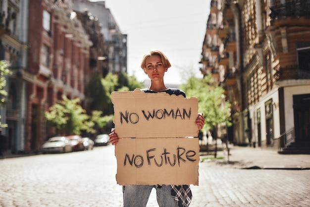 여자는 서 있는 동안 여자가 없는 미래가 없는 간판을 들고 있는 젊은 여성에게 힘을 준다