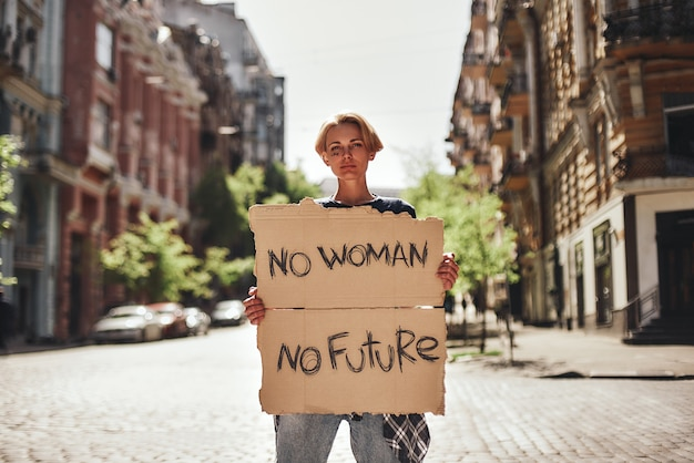Women power young female holding a signboard with word no woman no future while standing