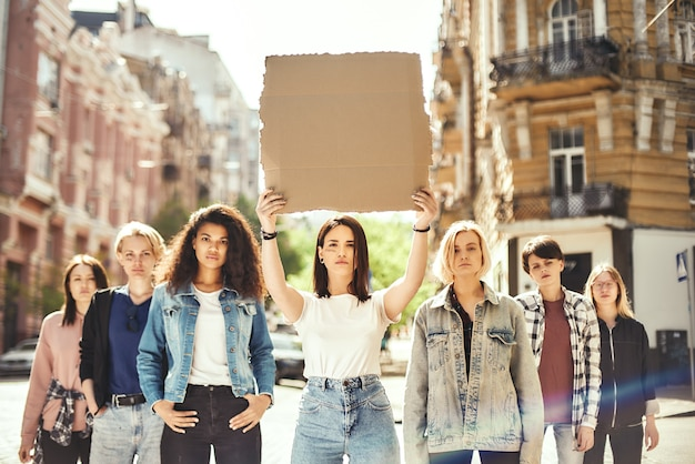 Women power young woman is holding blank signboard over her head while standing on the
