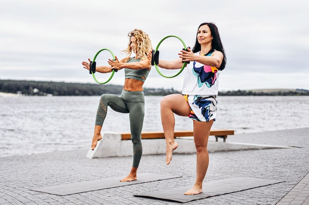 Women practice yoga exercises on a mat with a special sports circle