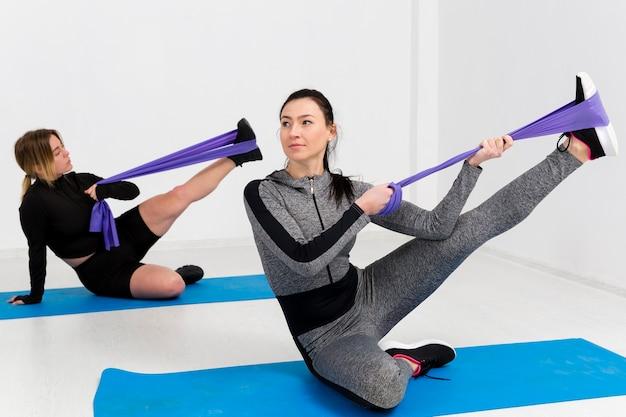 Женщины тренируются на коврике в тренажерном зале