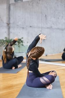 Women practicing practicing lotus pose in hall.