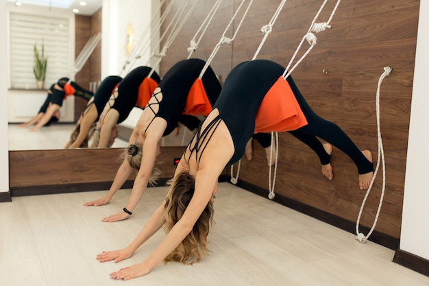 Women practicing yoga on ropes stretching in gym. fit and wellness lifestyle