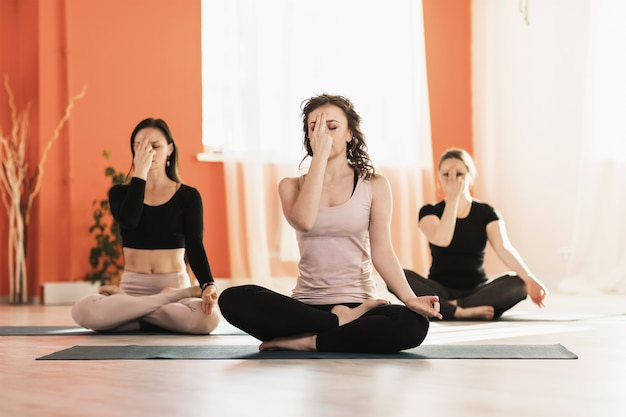 Women practicing yoga sitting in the lotus position doing meditation and breathing exercises pranayama in the studio