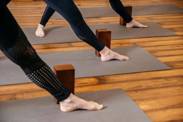 手で木製のブロックを使用してヨガのストレッチを練習している女性、背骨と肩の運動