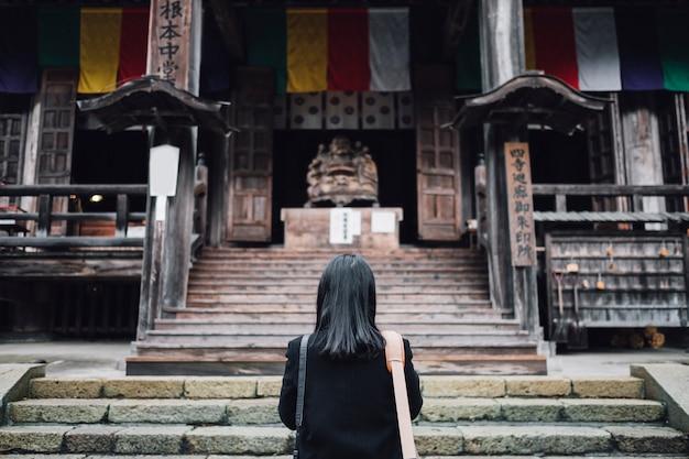 女性が日本の神社で祈る