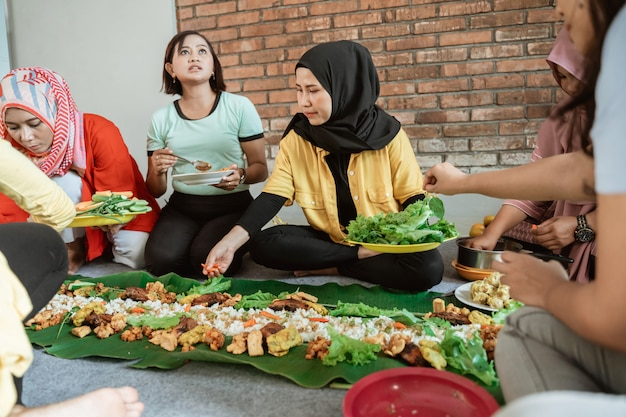 自宅で友達と夕食の準備をしている女性