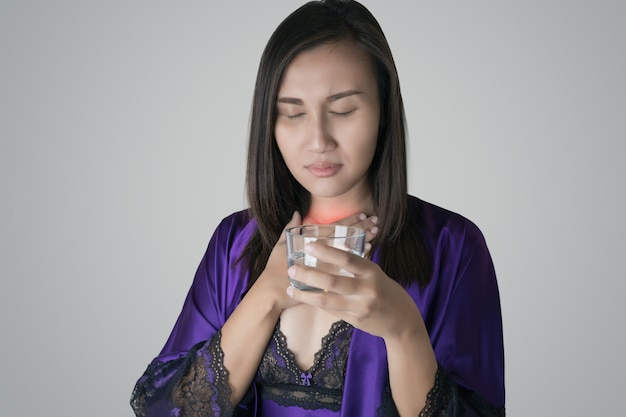 Women in purple silk nightwear and purple robe holding a glass of water have a sore throat due to the dry throat at night